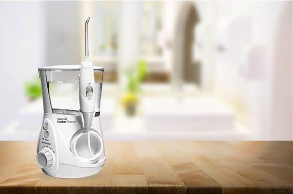 Man using a waterpik wp -660 water flosser in the bathroom