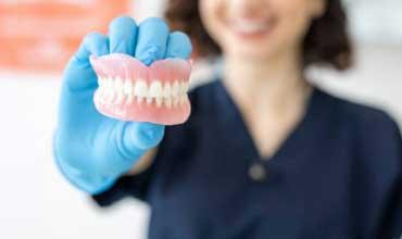 dentist holding upper and lower dentures